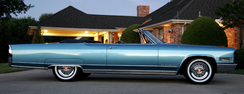 1966 Cadillac with chrome wire wheels and wide whitewall tires.